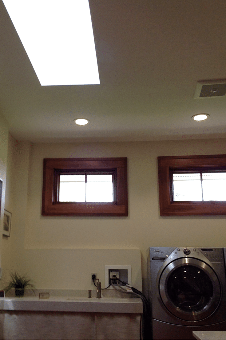 Natural lighting using transom windows and an operable skylight in a universal design custom closet