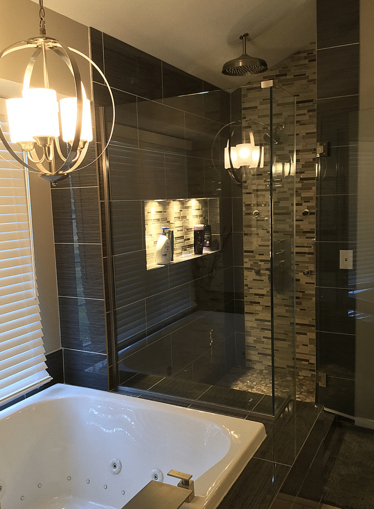 A contemporary bathroom remodel in Upper Arlington Ohio with large format tiles and a chandelier | Innovate Building Solutions and Innovate Home Org Columbus Ohio