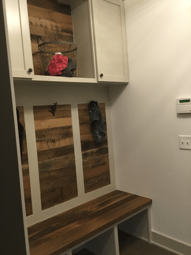 Wood feature wall in a mudroom storage system Manor Homes | Innovate Home Org | Innovate Building Solutions | #FeatureWall #MudroomDesign #EntrywayStorage